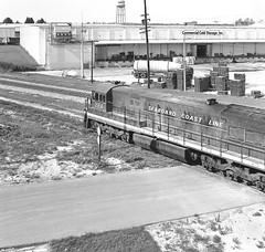 SCL GE U30C locomotive # 2124, is seen from the U.S. 92  Highway overpass at Auburndale, Florida, June 9, 1973 (alcomike43) Tags: scl seaboardcoastline sal seaboardairline acl atlanticcoastline railroad trains freighttrains auburndaleflorida us92 highwayoverpass road gradecrossing warehouse tracks mainlines rightofway conventionaljointedsectionrail ties rails ballast roadbed street locomotive engine diesel u30c ge dieselelectriclocomotive diesellocomotive dieselengine photo photograph negative bw blackandwhite old historic vintage classic 2124