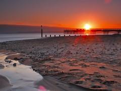Boscombe Light (James Whitlock Photography) Tags: uk longexposure light sunset sea cloud sun beach silhouette coast pier stream dusk streetlamp footprints pebbles coastline groyne boscombe dorest 10stop