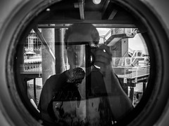 Porthole Portrait (Jason Gallant.) Tags: old blackandwhite bw selfportrait reflection mannequin window metal museum stairs canon circle eos boat ship waterfront framed porthole boardwalk steamship posts retired fraserriver newwestminster paddlewheeler 18200mm 60d samsonv rallings tgam:photodesk=reflection2013