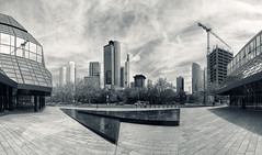 Skyline Panorama (Philipp Klinger Photography) Tags: park street trees light shadow sky bw panorama sculpture white black building tree tower fountain lines car weather skyline architecture clouds skyscraper silver