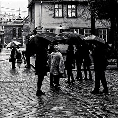 umbrella  conversation (travelben) Tags: street city urban bw wet rain architecture rural umbrella walking town europe outdoor pavement pluie eu baltic nb latvia rainy older paving rue ville riga paved parapluie lettonia pav lettonie balte