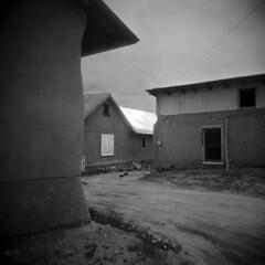 Truchas #3 (LowerDarnley) Tags: holga newmexico truchas highroad houses adobe roof metallic road southwest sun