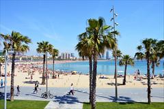 Beach time 2 (angelsgermain) Tags: sea summer sky people sunlight building beach fun sand bikes catalonia palmtrees shade umbrellas lampposts bercelona platjedesantsebasti laberceloneta