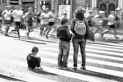 Marathon (halifaxlight (back in March)) Tags: madrid street bw woman motion blur children spain crossing shadows sunny runners spectators soe granvia flickraward madridmarathon theperfectphotograper