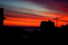Sunset In Sliema, Malta (Explored) (Butch Osborne) Tags: city sunset red sky nature silhouette skyline clouds buildings fire skies cityscape view rooftops crane awesome malta explore 1001nights magnificent sliema explored malta2012