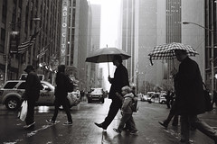 Walking in his Father's Footsteps (Airicsson) Tags: street leica city nyc newyorkcity urban blackandwhite bw newyork rain analog america umbrella 35mm vintage kodak manhattan trix center midtown summicron symetry radiocitymusichall m6 6thavenue rockfeller avenueoftheamericas