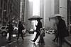 Walking in his Father's Footsteps (Airicsson) Tags: street leica city nyc newyorkcity urban blackandwhite bw newyork rain analog america umbrella 35mm vintage kodak manhattan trix center midtown summicron symetry radiocitymusichall m6 6thavenue rockfeller avenueoftheamericas