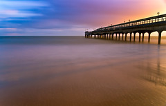 Sunset Blur (paulwynn-mackenzie.co.uk) Tags: longexposure sunset england seascape blur color colour slr colors clouds digital reflections landscape photography golden pier interesting colours sony kitlens sigma a33 sharp le dorset 1855mm alpha dslr 1020mm bournemouth slt boscombe goldensand