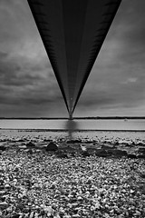 Under The Bridge (mark_mullen) Tags: uk blackandwhite beach water lights mono rocks crossing hull span humberbridge eastyorkshire canon1740f4 canon1dsmkii riverhumber bartononhumber markmullenphotography hesslewaterfront