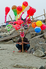 I sell only fun. (Pagan Eyes) Tags: boy portrait beach toy colorful sad mask candid crowd balloon tourist tired question gathering isolation curious posture bd curiosity bangladesh hawker touristspot isolate ch