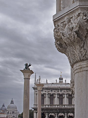 Rita Crane Photography:  Italy / Venice / architecture / sculpture / St. Mark the Lion  / Icons of Venice, Piazza San Marco (Rita Crane Photography) Tags: venice winter italy architecture facade icons pigeon statues stonecarving venezia greysky piazzasanmarco stockphoto stmarkssquare santamariadellasalute stmark stockphotography wingedlion sanmarcosquare columnofsanteodoro lionofvenice ritacranephotography wwwritacranestudiocom symbolofvenice theprocurate procuritie dogepalacecolumns sttheodorestatue