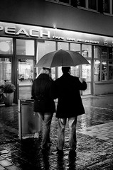 Where To? (andersdenkend) Tags: street city urban blackandwhite black wet caf rain stone bar night umbrella reflections couple availablelight pair paar peach bistro cobble vignetting moist artificiallight nikkor50mmf12 nikond700