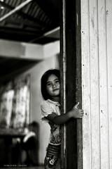 Shy Smile (Manic~Mind) Tags: street door camera sea people bw white house black girl smile island wooden kid nikon child candid shy human malaysia peek dslr malaysian sabah spontaneous d90 sabahan pulaugaya yusriyusof