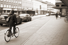 Make way for the cyklist! [Explored] (Issa Fakhro) Tags: road city people urban bw man cars sepia canon vintage 50mm dof traffic natural sweden bokeh pavement candid snapshot january streetphotography motionblur lane panning malm bicykle 2012 blackandwhitephotography cyklist vrnhemstorget vrnhem