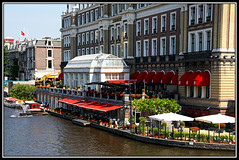Red Canopies (Audrey A Jackson) Tags: trees windows red plants holland water amsterdam buildings boats hotel canal tables umbrellas canopies canon450