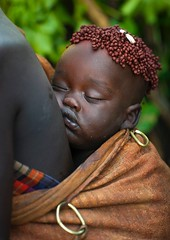 Ethiopia. A Bodi tribe baby fast asleep.  The 'coffee bean' hairstyle is often seen in the region.  Hana Mursi, Omo Valley //   Eric Lafforgue (mike catalonian) Tags: africa portrait color face children photography ethiopia bodi ericlafforgue easternregion