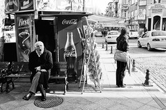 Tired? How about a bottle of Coke? (FreakyLeo) Tags: life road street city light people bw sun man cars contrast turkey bench europe coke istanbul explore sidewalk advert chilly gasp explored pentaxk5 pentaxda21mm132allimited explore29jan2012