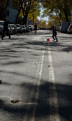 Red Ball (seanjonesfoto) Tags: street nyc trees red portrait people playing ny newyork color fall leaves lines silhouette kids brooklyn ball d50 children 50mm nikon perspective nycmarathon quotes gothamist nikkor streetscape fortgreene