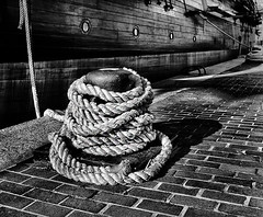 USS Constellation at the Pier in Maryland (` Toshio ') Tags: blackandwhite bw brick history speed harbor pier pattern ship control rope baltimore line deck porthole cannon historical hull tallship bollard constellation ussconstellation moored toshio x100 musictomyeyeslevel1