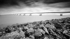 Zeeland Stonecoast Mono (frank_w_aus_l) Tags: longexposure bridge sky bw seascape water netherlands monochrome stone architecture clouds wideangle zeeland nl brilliant niederlande zeelandbrug colijnsplaat nikond810