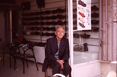 This is Mr. Farahani, the shoe business (futile81) Tags: sun man film 35mm canon store chair shoes iran esfahan eos5 businesses