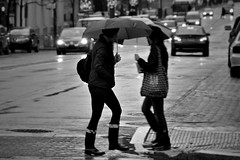 casually ignoring one another in passing (damonabnormal) Tags: street city people urban blackandwhite bw philadelphia wet nikon women december boots candid snapshot streetphotography pa rainy philly umbrellas phl passerby commuters urbanite brollies 2011 d90