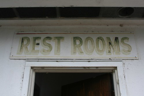 Faded vintage rest rooms sign on cabana