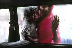 Steve McCurry / Magnum Photos (Hotels-HPRG) Tags: poverty pink window wet rain automobile child hand interior touch mother beggar monsoon bombay curiosity sari twopeople looksee seenthrough moodyatmospheresensation woman18to25years womanallages childbeingcarried asiansouthasianorigin indianinhabitantofindianationality babygirl0to3years
