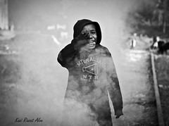Smile behind smoke......... (y) (Kazi Riasat Alve) Tags: street winter boy bw canon 50mm prime candid smoke homeless bangladesh chittagong 500d flickraward kissx3 kaziriasatalve chittagongrailwaystation