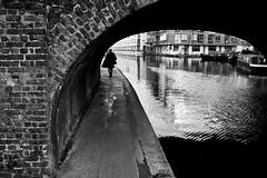 Under St. Peters Street (Gary Kinsman) Tags: stpetersstreet islington london n1 canon350d canon1855mm canal regentscanal bridge back candid streetlife streetphotography man coat bw blackwhite tunnel water follow stalk watch stpeter canonrebelxt 2007 people person