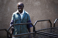 This young man painted the 20 steelbeds that had been made in Kimilili out of the money 4 swedish girls had collected (Diana Savina) Tags: africa people man wall bed humanity kenya beds young photojournalism mount painter photojournalist elgon peopleoftheworld peopleofafrica kimilili