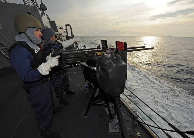 A Sailor mans a mounted machine gun.