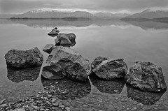 Milarrochy Rocks (2) (w.mekwi photography [on the road]) Tags: blackandwhite bw water landscape scotland hills snowcapped boulders lochlomond milarrochybay nikkor18105mm nikond7000 wmekwiphotography mekwicom milarrochyrocks