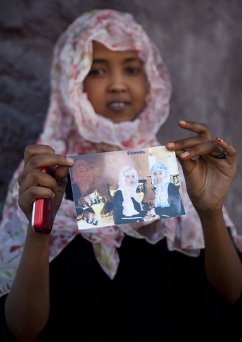 Veiled Teenage Girl Showing Photo Of Her With A Friend, Boorama Somaliland