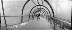 Leaving the Mothership (*monz*) Tags: road street bridge people blackandwhite bw streets circle iso800 store birmingham arch mesh pedestrian tunnel 150 selfridges walkway widelux push hp5 swinglens rodinal ilford department brum 20c perspex f7 16m 26mm monz panon 1stop autaut