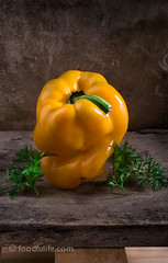 Bell pepper with carrot leaves (foodfulife) Tags: wood stilllife food colour texture beautiful vegetables leaves yellow vertical fruit big interesting creative large photographic fresh peppers organic shape oldwood bellpepper peppercorn woodenboard foodphotography comosition fruitandvegetables carrotleaves