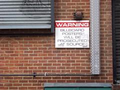 prosecuted at source (JudyGr) Tags: brick london sign metal wall warning billboard posters shutters guesswherelondon londonguessed gwl guessedbytrailerfullofpix willbeprosecuted