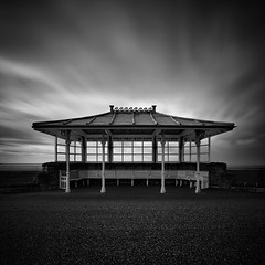 Shelter (Andy Brown (mrbuk1)) Tags: longexposure windows roof cloud wall contrast square mono blackwhite seaside movement pavement central somerset symmetry busshelter seats benches ornamental simple vignette tone westonsupermare bold neutraldensity 10stop