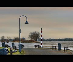 Who's relaxing at the riverside (Wim K) Tags: trees light red sky lighthouse holland water netherlands dutch river bench relax photography photo nikon waves view horizon stock nederland bin pole sit flowing lantern waste rhine beacon rijn wastebin stockphoto waal stockphotography gorinchem d90 lightbeacon wpk wpk2