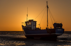Doing a proper job (SiKenyonImages) Tags: light sunset shadow orange yellow dark boat wirral merseyside meols