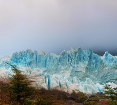 Glacier in the Fog (Stuck in Customs) Tags: travel blue trees wild sky panorama patagonia white mountain snow mountains cold ice argentina argentine digital america outdoors photography march frozen blog high dangerous republic dynamic stuck natural hiking south scenic freezing hike glacier formation clear photoblog crisp software processing andes imaging iceberg geology wilderness icy frigid range 2009 hdr repblica tutorial rugged harsh travelblog customs cobalt foothill argentino glacial hdrtutorial stuckincustoms photographyblog stuckincustomscom nikond3x