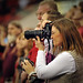 A mom takes photos of her ROTC graduating son during commencement.