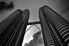 Tower of the Titans. (Silent Resilience) Tags: petronas towers towering sky dark drama clouds storm tall goliath malaysia tallest buildings architecture kl kualalumpur city world icon wonder famous structure blackwhite black white bw monochromatic nikon farah silentresilience