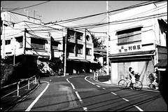 A corner in Higashi-Kitazawa (Eric Flexyourhead) Tags: street city urban bw woman girl bicycle japan japanese tokyo blackwhite child mother   streetscape  setagaya  setagayaku mamachari grainyfilm artfilter higashikitazawa charinko olympusep1 panasoniclumix20mmf17