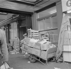 Boxes (Tyne & Wear Archives & Museums) Tags: newcastle 1970s blackandwhite emptyboxes blackswan wheelbarrow apples grocery crates workingenvironment streetphotography boxes blackandwhitephotograph roberthopecollection digitalimage socialhistory industry industrial abstract roberthope photographer newcastleupontyne early1970s rolleiflexcamera newcastlescenes cart wheel handle grip tyre bag arm hand coat crease pavement debris pile timber nail bar metal paper shop display window glass buildings signage letter sign door ceiling roof wall ground land cloth padlock chain pedestrian artificiallight daylight consumerism retail business premises city reflection interesting fascinating unusual poignant streetscene northeastofengland
