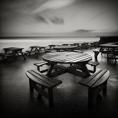 Tables (Andy Brown (mrbuk1)) Tags: ocean longexposure light sea cloud wet rain tarmac reflections square dawn mono blackwhite wooden devon seats repetition benches tones vignette mundane paignton leefilters bwfilters