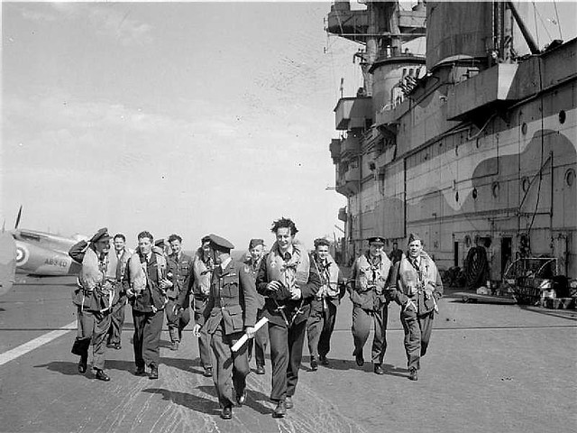 Operation PICKET I: RAF pilots walk towards their aircraft on the flight deck of HMS EAGLE after receiving their final instructions, before flying a reinforcement of nine Supermarine Spitfires to Ta Kali, Malta.