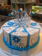 Wicked Chocolate cake iced in white butter icing decorated with blue fondant stripe panels, blue & white op art daisies, silver piped dotty hearts, 3D silver #19, toy silver tiara & wired hearts (Charly's Bakery) Tags: birthday tiara cake town tv princess chocolate wicked angels bakery reality cape teenage charlys october2010