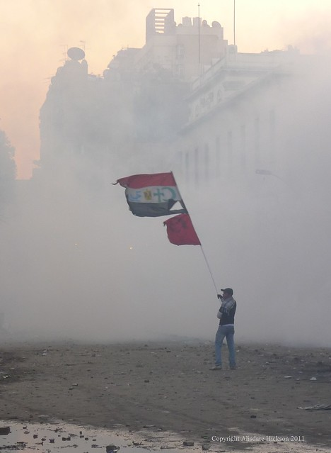 A protester defiantly waves an Egyptian flag with the emblems of Christianity and Islam (the cross and the crescent) added - a message of religious unity.    Clouds of tear gas in the background.