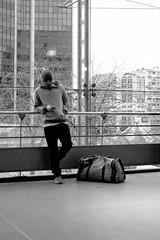 L'attente  la Gare Montparnasse (Paolo Pizzimenti) Tags: paris film commerce paolo gare olympus casquette f18 montparnasse gens omd vitrine argentique 25mm em1 attente pellicule 17mm m43 verrier mirrorless
